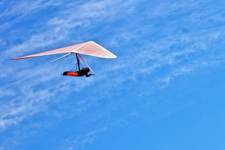 Hang gliding man on a white wing in a bright blue sky