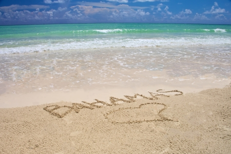 bahama: Tropical beach in Bahamas - bright blue sky, turquoise water and writing on the sand Stock Photo