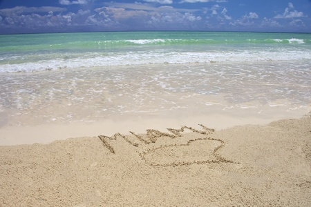 Tropical beach in Miami - bright blue sky, turquoise water and writing on the sand photo