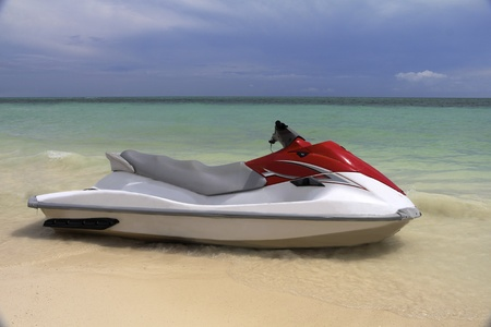 Jet Ski waiting at the shore on a tropical beach photo