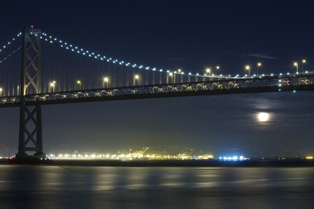 Moon Rising Under San Francisco Bay Bridge on an almost clear night. The bridge is lit up by yellow and blue lights