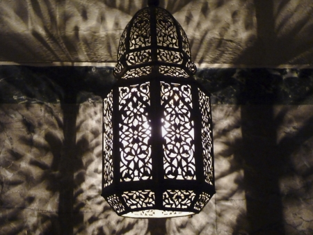morocco: Moroccan Ornate Pierced Metal Filigree Lamp casting intricate shadows on the wall