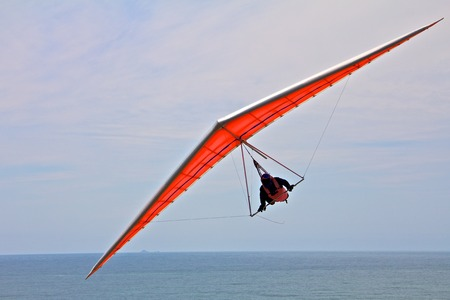 gliding: Hang gliding man on a white wing with sky in the background Stock Photo