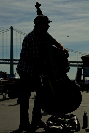 Silhouette of a contrabass player with the Bay Bridge in the background Stock Photo
