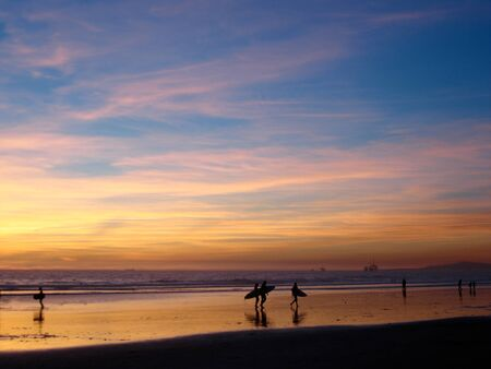 huntington beach: Yellow and pink whispy clouds of sunset and silhouettes of surfers create a feeling of serenity