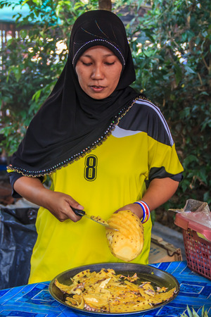Muslim woman slicing fresh pineapple at the Market in Krabi Town, Thailand