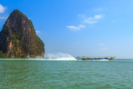 Longtail boat in Krabi Thailand, with limestone islands in the background photo