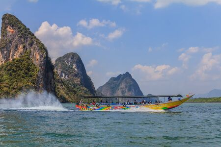 Longtail boat in Krabi Thailand, with limestone islands in the background