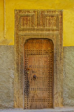 doorframe: Old wooden intricately carved, studded door and door-frame,of a traditional Moroccan house in Fes, Morocco