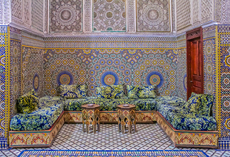 Fes, Morocco - May 11, 2013: Courtyard decorated with ornate mosaic and arabesque carvings, with traditional couches in a Moroccan riad Editorial