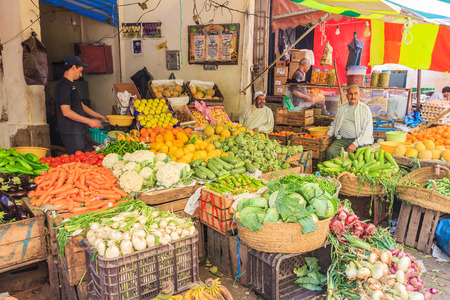souk: Fes, Morocco - May 11, 2013: Men selling vegetables at a stand in the souk, Moroccan market in the medina Editorial