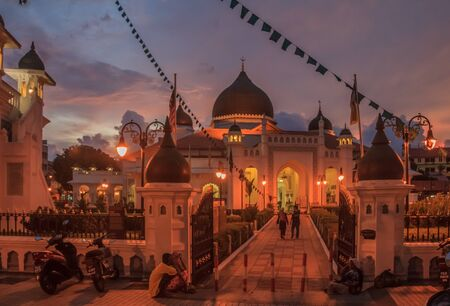 Georgetown Penang Malaysia  August 17 2013: People walking into the Kapitan Keling Mosque after sunset Редакционное