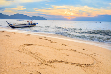 Tropical beach in Malaysia with bright sunset in the background a boat in the ocean and a heart drawn in the sand Фото со стока
