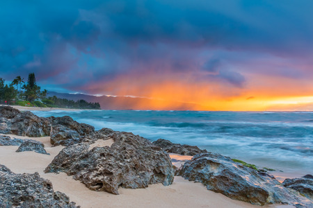 beach paradise: Skies on fire at sunset, with the rain in the background in North Shore, Oahu, Hawaii Stock Photo