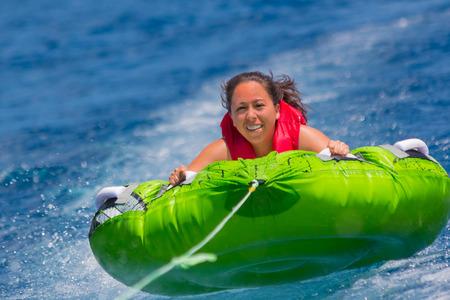 inner tube: Young girl enjoys a ride on an inner tube on lake Tahoe Stock Photo
