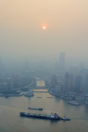 Shanghai, China - June 16, 2013: View of heavily polluted skyline over Huangpu river. Heavy air pollution has become common in many cities in China. Редакционное