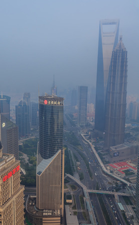unearthly: Shanghai, China - June 16, 2013: View of heavily polluted skyline. Heavy air pollution has become common in many cities in China. Shanghai World Financial Center and Jinmao Tower in the background