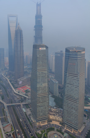 smog: Shanghai, China - June 16, 2013: View of heavily polluted skyline. Heavy air pollution has become common in many cities in China. Shanghai World Financial Center and Jinmao Tower in the background