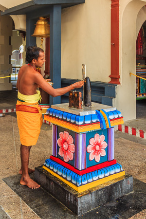 divali: Singapore, SIngapoe - June 19, 2013:  Hindu worshiper at an altar in the Sri Mariamman hindu temple in Singapore Editorial