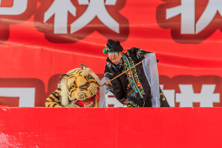 show folk: Chinese puppeteer performing a hand puppet show about Wu Song killing the man-eating tiger based on an ancient Chinese folk story