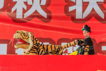 puppeteer: Chinese puppeteer performing a hand puppet show about Wu Song killing the man-eating tiger based on an ancient Chinese folka story Stock Photo