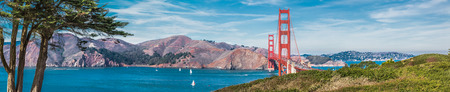 Panorama of the Golden Gate bridge in clear blue sky with green grass as foreground in San Francisco, USA Фото со стока