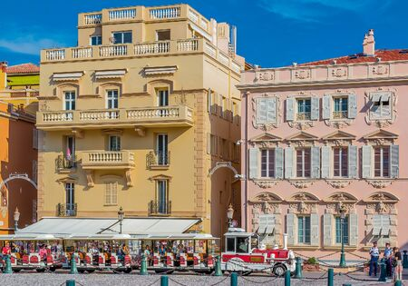 trackless: Monaco Ville, Monaco - October 7, 2016: Red and white trackless train of Monaco in front of the princial palace. The Palace Square or Place du Palais is among most popular destinations in Monaco Editorial