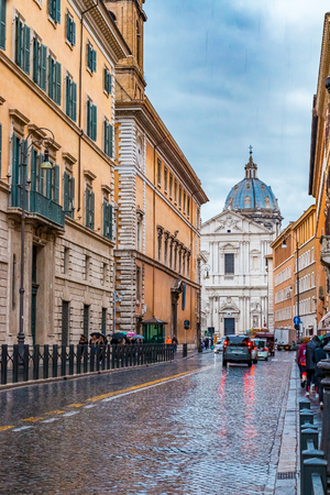 Rome, Italy - October 13, 2016: Narrow cobblestone street wiith the view onto a basilica dome on a rainy day in Centro Storico in Rome Italy