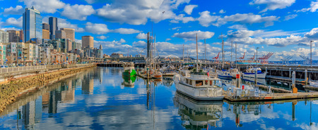 puget: Seattle, USA - February 28, 2017: Panoramic view of Seattle waterfront with the skyline of piers, skyscrapers and Ferris wheel on a bright sunny day with clouds Editorial