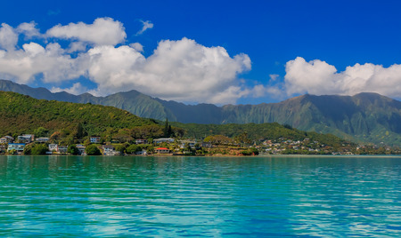 Panoramic view of a tropical lagoon and lush mountains in contrast with the ocean in Oahu, Hawaii Stock Photo