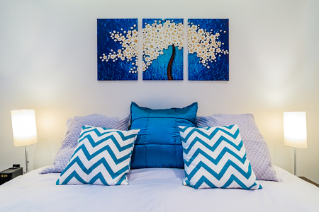 bedspread: Large bed with linnens and bright blue pillows in a modern bedroom, wall art painting and lights
