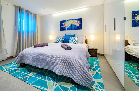 bedspread: Large bright modern bedroom with a king size bed, decorated in green and blue tones with pillows, wall art painting, rug and welcoming towels Stock Photo