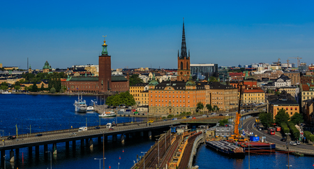 Panoramic view onto traditional gothic buildings in the old town, Gamla Stan; Riddarholmen island with burial church of Swedish monarchs and City Hall, Stadshuset, in Kungsholmen island in Stockholm, Sweden