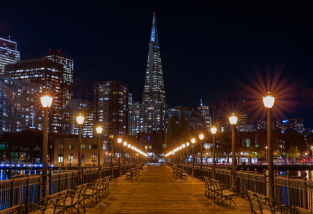 San Francisco, USA - November 27, 2017: Scenic view of the Embarcadero Buildings, decorated for Christmas, downtown San Francisco and the Transamerica Pyramid from the famous romantic wooden Pier 7 at sunset Editorial