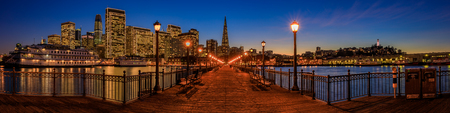 San Francisco, USA - November 27, 2017: Panoramic view of the Embarcadero Buildings, decorated for Christmas, downtown San Francisco and the Transamerica Pyramid from the famous romantic wooden Pier 7 at sunset