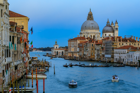 Sunset at the iconic 17th-century Santa Maria di Salute Basilica, view from Academia bridge or Puente de la academia along the Grand Canal in Venice, Italy