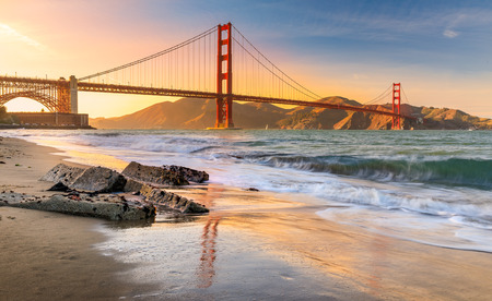 Exposición prolongada de una impresionante puesta de sol en la playa junto al famoso Puente Golden Gate en San Francisco, California