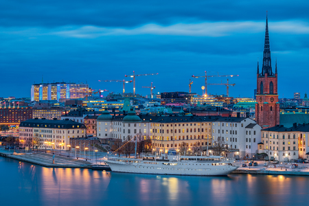 Stockholm, Sweden - October 24, 2017: Sunset view over Lake Malaren onto traditional gothic buildings in old town, Gamla Stan and Riddarholmen church, burial church of Swedish monarchs. Long exposure