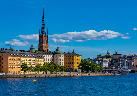 View across Lake Malaren onto traditional gothic buildings, across Lake Malaren, in the old town, Gamla Stan in and Riddarholmen church, the burial church of Swedish monarchs in Stockholm, Sweden