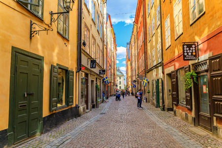 Stockholm, Sweden - August 14, 2017: Tourists walking in the medieval alleyways, along cobbled streets, and archaic architecture in the heart of the old town, Gamla Stan Editorial