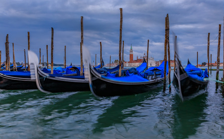 Gondolas along the picturesque Grand Canal at Piazza St Marco or Saint Mark's square at sunrise with the San Giorgio Maggiore church in the background n Venice Italy