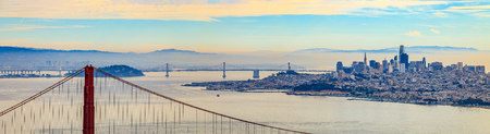 Panorama of the Golden Gate bridge on a cloudy day with the Marin Headlands in the foreground and San Francisco skyline in the background