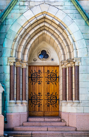 Ornate side door with intricate metal ornament at Oscarskyrkan or Oscar's Church which has an 80 meter high tower in the south-western part of the building, in Stockholm, Sweden Stock Photo