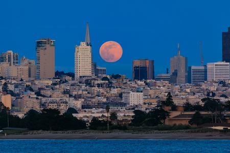 Panorama of pink moonrise above San Francisco Downtown landmarks viewed from Marina District in San Francisco, California, USA