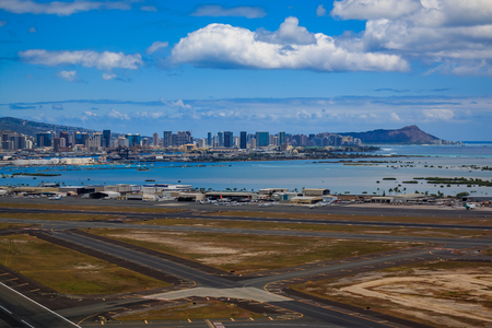 Aerial view of downtown Honolulu, Diamond Head and the runway of Daniel K. Inouye International Airport (HNL), formerly known as Honolulu International Airport in Hawaii from a helicopter Фото со стока