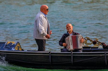 Venice, Italy - September 23, 2017: Man serenades gondola riders to an accompaniement of an accordeon
