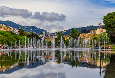 Nice, France - May 24, 2018: Reflecting fountain on Promenade du Paillon, surrounded by beautiful historic buildings and green urban park at Place Massena or Massena square 新聞圖片
