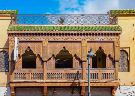 Ornate wood carved balcony and ironwork on the facade of a Moroccan riad in Marrakech, Morocco