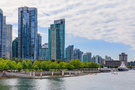Coal Harbor in Vancouver British Columbia with downtown buildings boats and reflections in the water