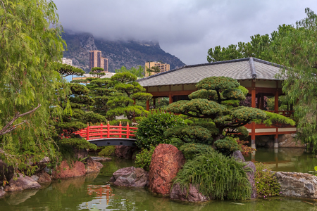 Monaco, Monte Carlo - October 13, 2013: Japanese Garden or Jardin Japonais with residential buildings in the background